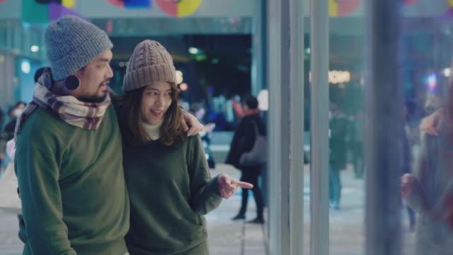 夜に街で窓の買い物を見ている若いカップル。 - デート点の映像素材/bロール