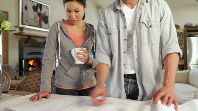 ms tu td young couple looking blueprints in their home / lamy, new mexico, united states - lamy new mexico stock videos and b-roll footage