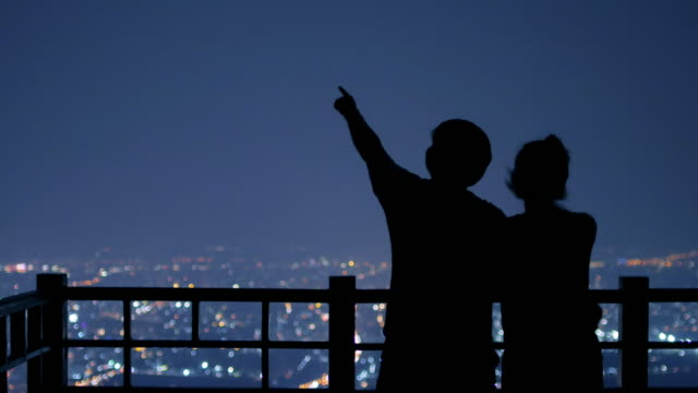 Young couple looking for Star on the background of the city at night , 4k(UHD)