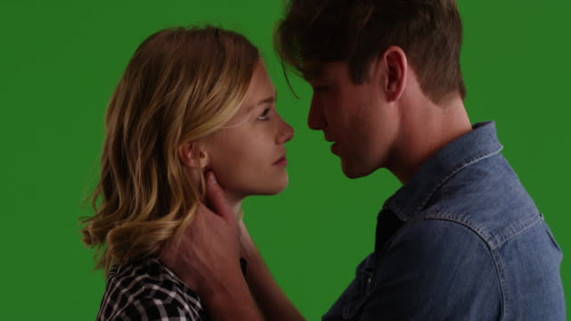 young couple looking into each other's eyes then kissing on green screen - küssen stock-videos und b-roll-filmmaterial