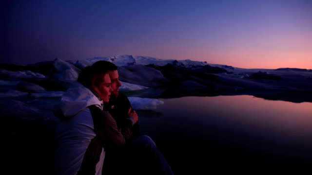 stockvideo's en b-roll-footage met ms young couple looking out on glacial lagoon at twilight, hofn, iceland - driekwartlengte