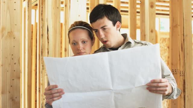 vidéos et rushes de young couple looking over the plans for their new home - plan d'architecte