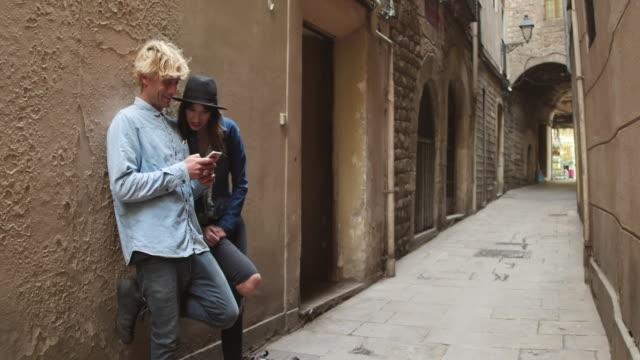 vídeos de stock e filmes b-roll de young couple looking social media at mobile phone on a narrow street in the city - dividir