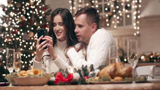若いカップルがクリスマステーブルでスマートフォンの写真を見ます。ゲストを待っている間、彼らは電話で両親や友人にクリスマスの挨拶を送信します。 - 整える点の映像素材/bロール