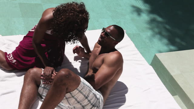 Young couple lying by swimming pool