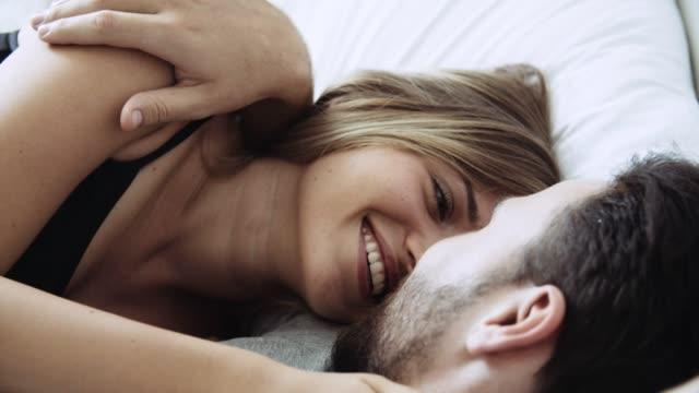vídeos de stock, filmes e b-roll de pares novos que encontram-se para baixo na cama e flertando - encarando