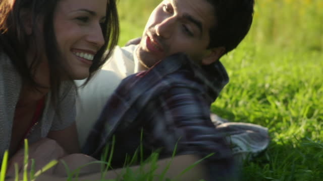 cu young couple lying in grass and talking, bovina center, new york, usa - fianco a fianco video stock e b–roll