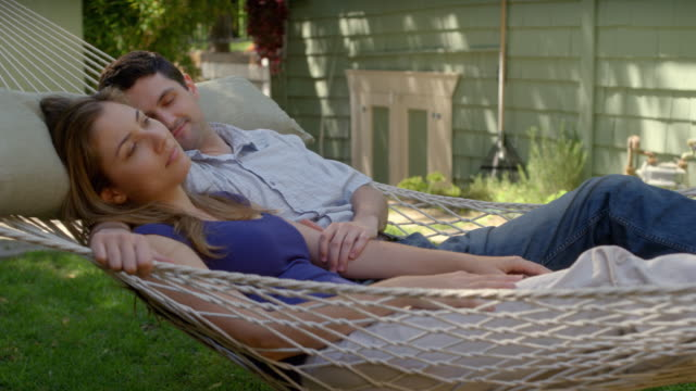 vidéos et rushes de ms young couple lying in hammock and relaxing in yard / los angeles, california, usa - hamac