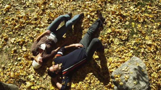 WS Young couple lying in leaves, kissing / Provo, Utah, USA