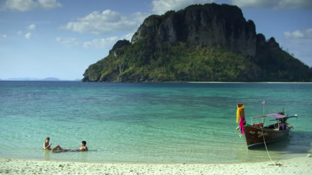 vídeos y material grabado en eventos de stock de ws young couple lying in shallow water on tropical beach, krabi, thailand - mar de andamán