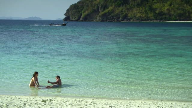 ws young couple lying in shallow water on tropical beach, krabi, thailand - see other clips from this shoot 1459 stock videos and b-roll footage