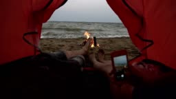 Young couple lying inside of the red tent. Close up footage of male and female legs. Girl is making a phote of their feet using a smartphone. Sea viewon the background