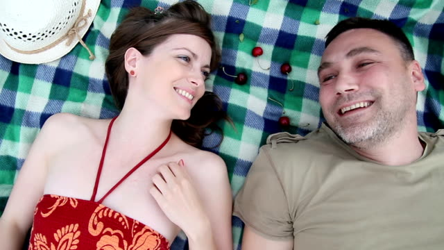 young couple lying on a picnic blanket - reclining stock videos & royalty-free footage