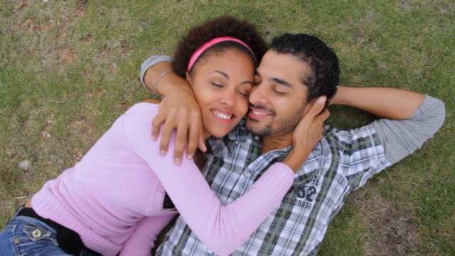 CU Young couple lying on grass, rubbing cheeks together and smiling / Havana, Cuba