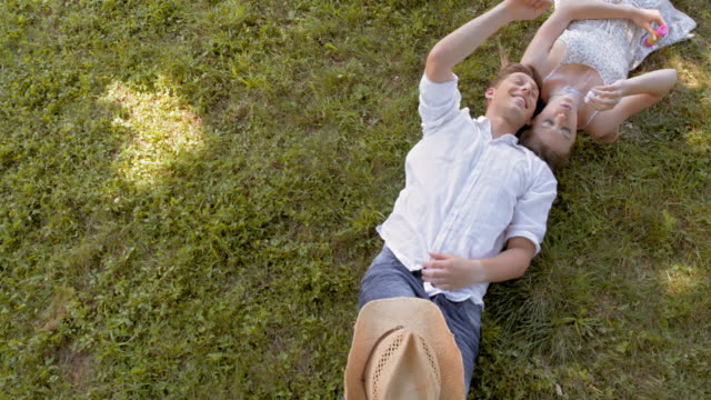 CS Young couple lying on the grass and making bubbles
