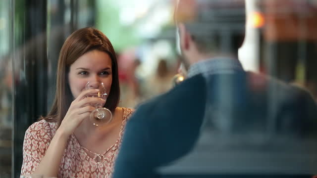 young couple make a toast and clink wine glasses in romantic parisian bistro. - flirting stock videos & royalty-free footage