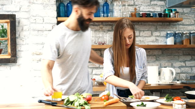 young couple making dinner together at home - cutting board stock videos and b-roll footage