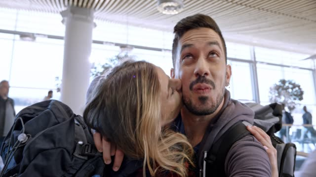 young couple making funny selfies from the gate at the airport while waiting for boarding - selfie video stock e b–roll