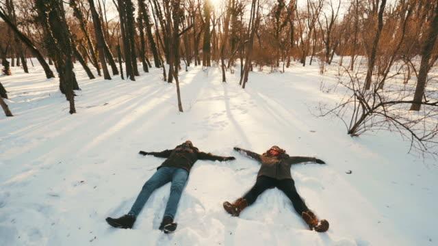 ungt par gör snöänglar. - människoarm bildbanksvideor och videomaterial från bakom kulisserna
