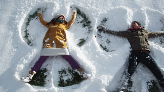 stockvideo's en b-roll-footage met young couple making snow angels - muts