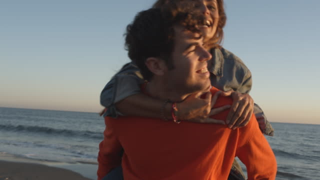 Young couple man carrying woman on back in sunset on beach