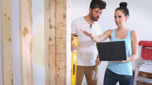 A young couple measure a wall during their renovation project.