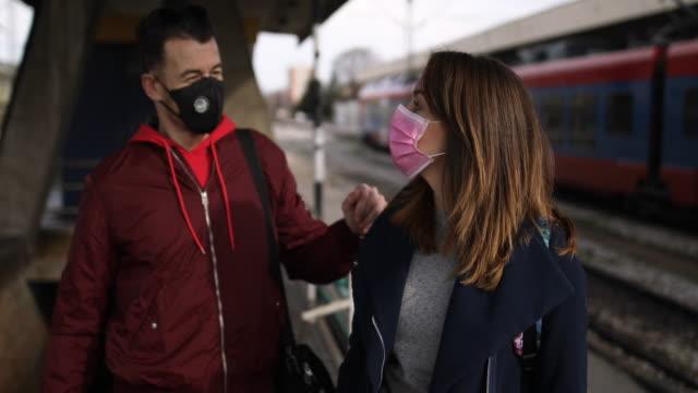 vídeos de stock, filmes e b-roll de jovem casal se encontrando e se beijando na estação de trem durante a manhã - perigo
