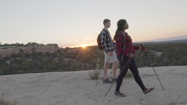 young couple mixed race millennials hiking using trekking poles on a giant rock formation at dusk near fruita colorado - western usa stock videos & royalty-free footage