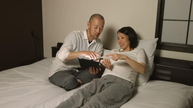 junges paar monitore schwangerschaft mit smartwatch - real wife sharing stock-videos und b-roll-filmmaterial