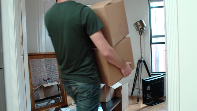 young couple moves in to new apartment - arranging stock videos and b-roll footage