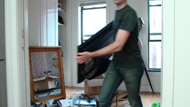 young couple moves in to new apartment - trasloco video stock e b–roll