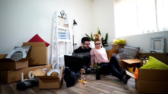 young couple moving in new home.sitting on floor and relaxing after cleaning and unpacking.looking something on laptop. - moving house stock videos and b-roll footage