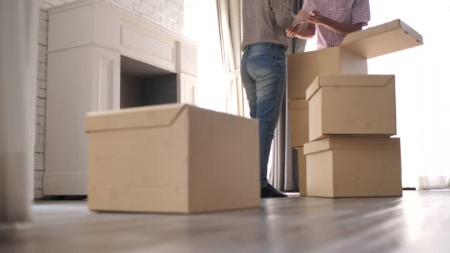 young couple moving in to new apartment - bricolage video stock e b–roll