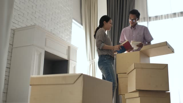 young couple moving in to new apartment - mixed race person stock videos & royalty-free footage