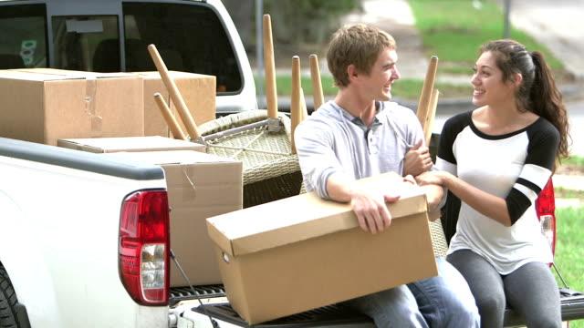 vidéos et rushes de jeune couple en mouvement, assis sur l'arrière de la camionnette - petite amie