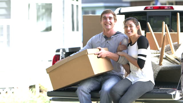 Young couple moving, sitting on back of pick-up truck