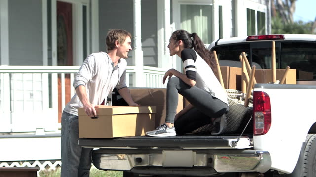 young couple moving, unloading boxes from pick-up truck - pick up truck stock videos and b-roll footage