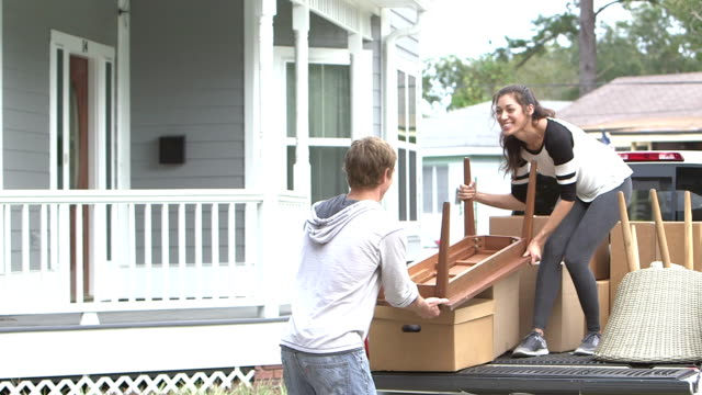 young couple moving, unloading table from pick-up truck - moving house stock videos & royalty-free footage