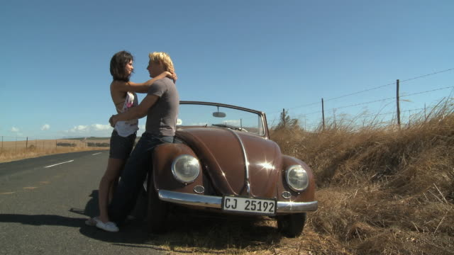 WS PAN Young couple next to car kissing / Cape Town, South Africa