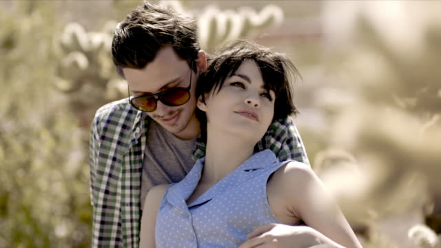 young couple nuzzle and kiss in cactus grove - cute cactus stock videos & royalty-free footage