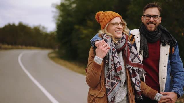 junges wanderpaar umarmt sich auf der straße - aktiver lebensstil stock-videos und b-roll-filmmaterial