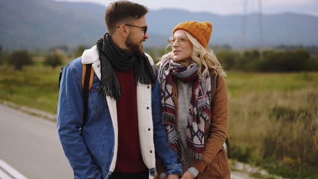 young couple of hikers hugging on the road - warm clothing stock videos & royalty-free footage