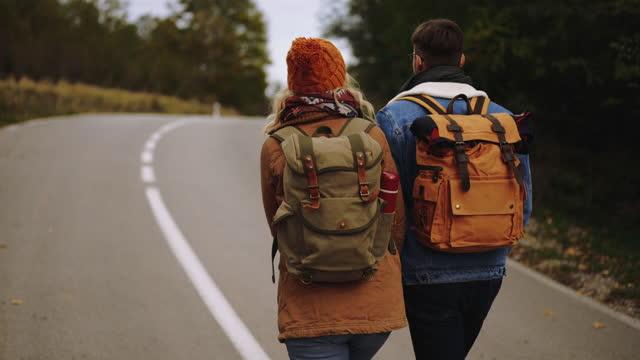 giovane coppia di escursionisti su strada di campagna - on the move video stock e b–roll