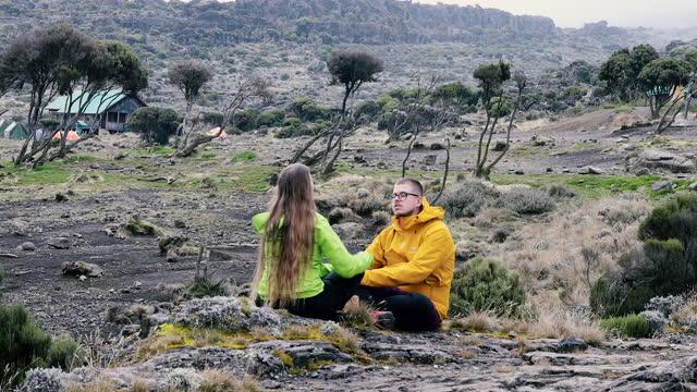 キリマンジャロへの道の風光明媚なキャンプ場で休むハイカーの若いカップル - キリマンジャロ山点の映像素材/bロール