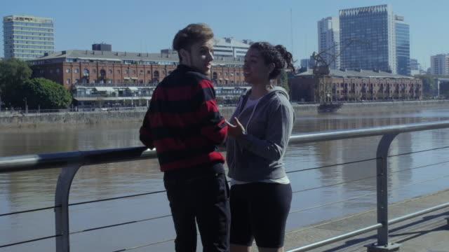 ウォーターフロントパークで陽気に抱き合うローラースケーターの若いカップル - プエルトマデロ点の映像素材/bロール