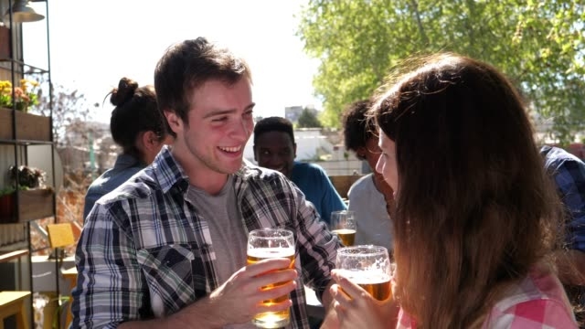 Young couple on a date at a bar flirting and talking while drinking a beer