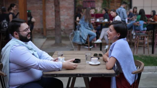 giovane coppia ad un appuntamento al bar all'aperto - overweight video stock e b–roll