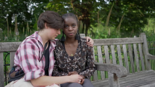 a young couple on a park bench having a heart to heart discussion, hugging each other and holding hands - uk stock videos & royalty-free footage