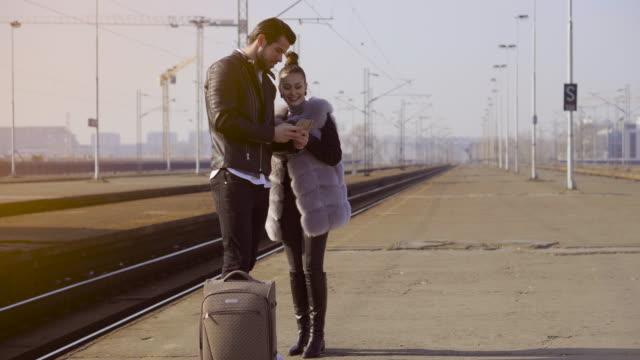 Junges Paar auf einem Bahnhof