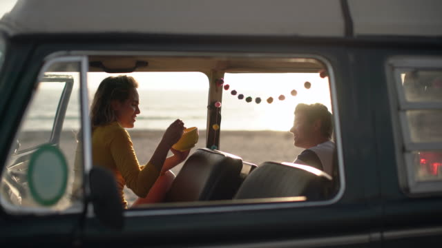 vidéos et rushes de ms young couple on a road trip in their camper van - camping